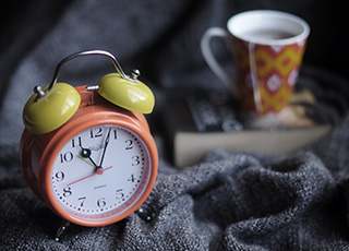 Old fashioned alarm clock and tea cup