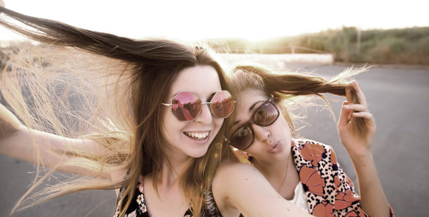 Two teen girls smiling outdoors