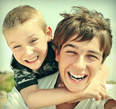 Two young boys smiling outdoors
