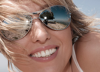 Smiling woman with sunglasses and beautiful teeth