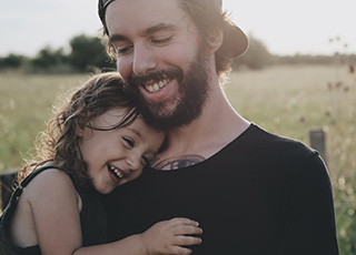 Smiling father and daughter outdoors