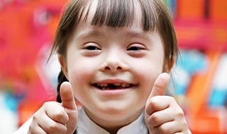 Little girl with special needs giving thumbs up